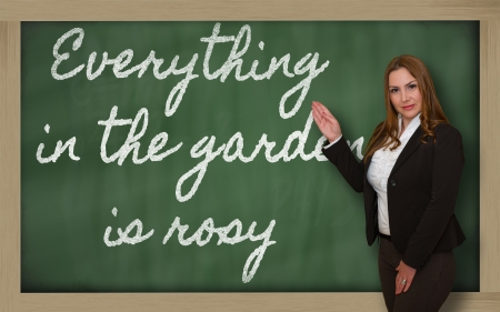 Successful, beautiful and confident woman showing Everything in the garden is rosy on blackboard