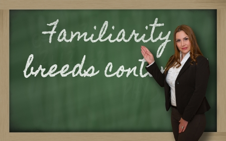 familiarity: Successful, beautiful and confident woman showing Familiarity breeds contempt on blackboard
