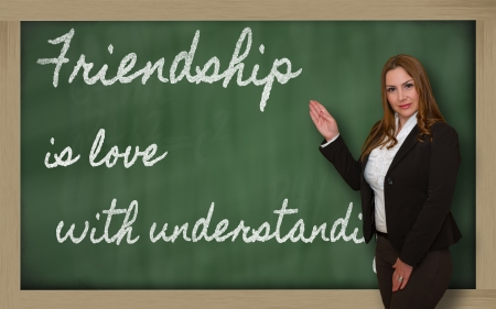 written text: Successful, beautiful and confident woman showing Friendship is love with understanding on blackboard