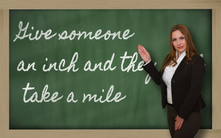 give and take: Successful, beautiful and confident woman showing Give someone an inch and they will take a on blackboard