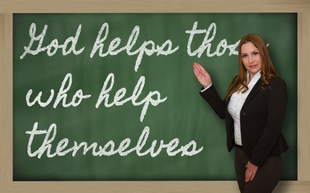 those: Successful, beautiful and confident woman showing God helps those who help themselves on blackboard
