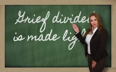 divided: Successful, beautiful and confident woman showing Grief divided is made lighter on blackboard