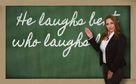 he laughs: Successful, beautiful and confident woman showing He laughs best who laughs last on blackboard Stock Photo