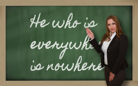 he: Successful, beautiful and confident woman showing He who is everywhere is nowhere on blackboard