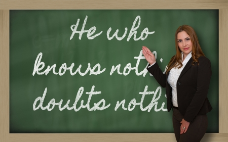 he: Successful, beautiful and confident woman showing He who knows nothing, doubts nothing on blackboard