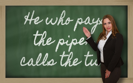 Successful, beautiful and confident woman showing He who pays the piper calls the tune on blackboard Stock Photo - 18660125