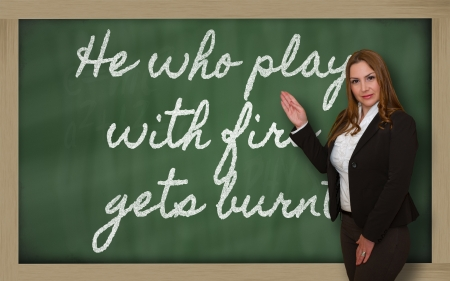 Successful, beautiful and confident woman showing He who plays with fire gets burnt on blackboard Stock Photo - 18660126