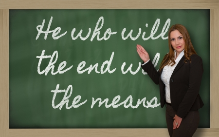 means to an end: Successful, beautiful and confident woman showing He who wills the end wills  the means on blackboard Stock Photo