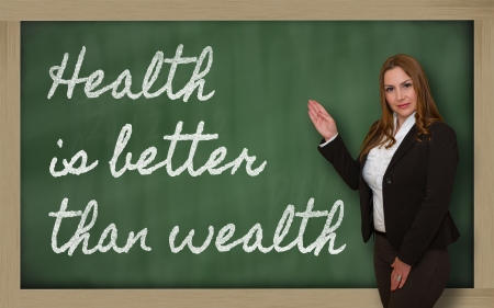 prudent: Successful, beautiful and confident woman showing Health is better than wealth on blackboard Stock Photo