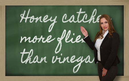 than: Successful, beautiful and confident woman showing Honey catches more flies than vinegar on blackboard