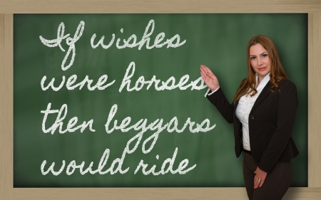 beggars: Successful, beautiful and confident woman showing If wishes were horses, then beggars would ride on blackboard