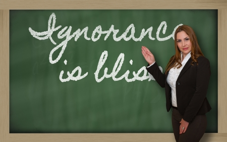 ignorance: Successful, beautiful and confident woman showing Ignorance is bliss on blackboard