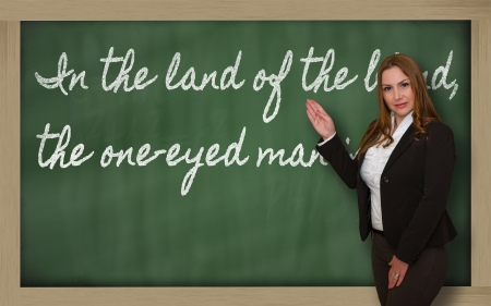Successful, beautiful and confident woman showing In the land of the blind, the one-eyed man is king on blackboard photo