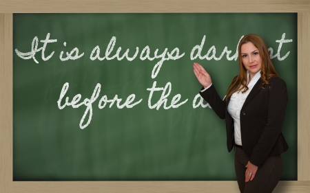 Successful, beautiful and confident woman showing It is always darkest before the dawn on blackboard Stok Fotoğraf