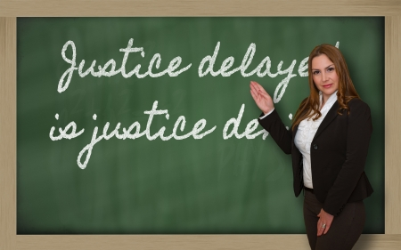 the delayed: Successful, beautiful and confident woman showing Justice delayed is justice denied on blackboard