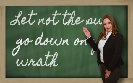 wrath: Successful, beautiful and confident woman showing Let not the sun go down on your wrath on blackboard