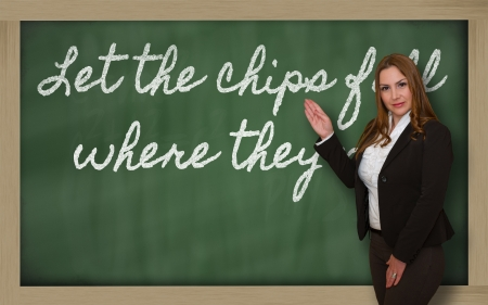 Successful, beautiful and confident woman showing Let the chips fall where they may on blackboard