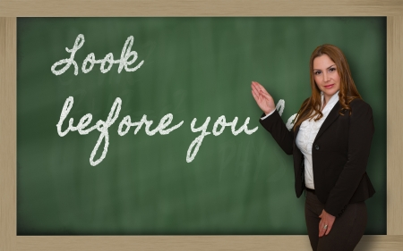 Successful, beautiful and confident woman showing Look before you leap on blackboard Stok Fotoğraf