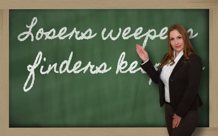 finders: Successful, beautiful and confident woman showing Losers weepers, finders keepers_blackboard on blackboard