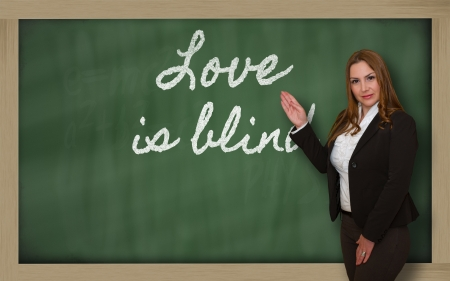 Successful, beautiful and confident woman showing Love is blind on blackboard photo
