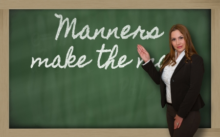 manners: Successful, beautiful and confident woman showing Manners make the man on blackboard Stock Photo