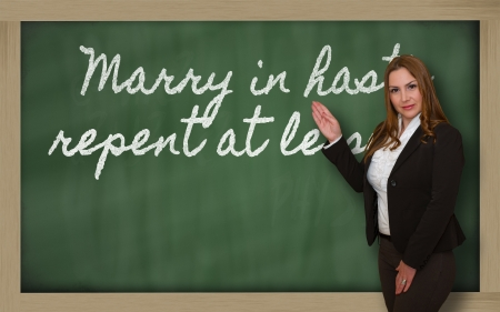 repent: Successful, beautiful and confident woman showing Marry in haste, repent at leisure on blackboard Stock Photo