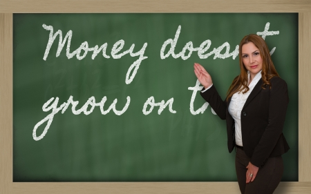 grow money: Successful, beautiful and confident woman showing Money doesn t grow on trees on blackboard Stock Photo