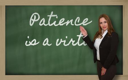 인내: Successful, beautiful and confident woman showing Patience is a virtue on blackboard
