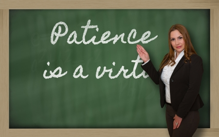 virtue: Successful, beautiful and confident woman showing Patience is a virtue on blackboard