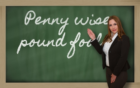 Successful, beautiful and confident woman showing Penny wise, pound foolish on blackboard