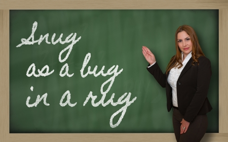 snug: Successful, beautiful and confident woman showing Snug as a bug in a rug on blackboard