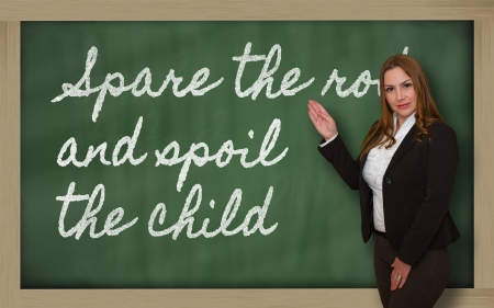 spoil: Successful, beautiful and confident woman showing Spare the rod and spoil the child on blackboard