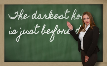 Successful, beautiful and confident woman showing The darkest hour is just before dawn on blackboard Stok Fotoğraf