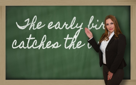 Successful, beautiful and confident woman showing The early bird catches the worm on blackboard