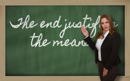 means to an end: Successful, beautiful and confident woman showing The end justifies the means on blackboard Stock Photo