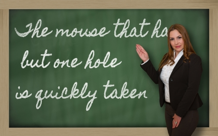 has: Successful, beautiful and confident woman showing The mouse that has but one hole is quickly taken on blackboard