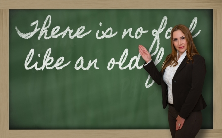Successful, beautiful and confident woman showing There is no fool like an old fool on blackboard