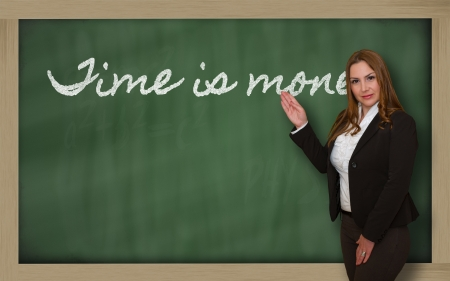 Successful, beautiful and confident woman showing Time is money on blackboard photo