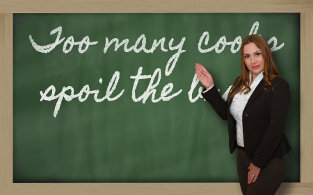 spoil: Successful, beautiful and confident woman showing too many cooks spoil the broth on blackboard