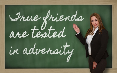 adversity: Successful, beautiful and confident woman showing True friends are tested in adversity on blackboard