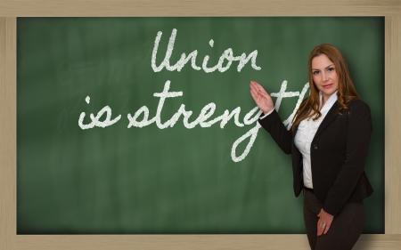 la union hace la fuerza: Mujer exitosa, hermosa y confiada que muestra la uni�n hace la fuerza en la pizarra