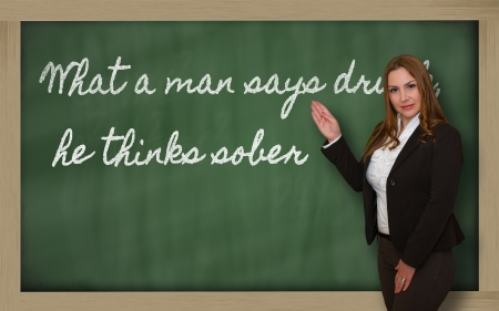 Successful, beautiful and confident woman showing What a man says drunk, he thinks sober on blackboard