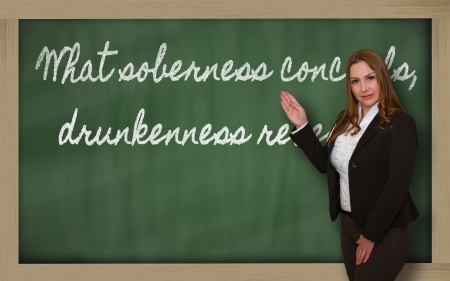 Successful, beautiful and confident woman showing What soberness conceals, drunkenness reveals on blackboard Stock Photo - 18708136