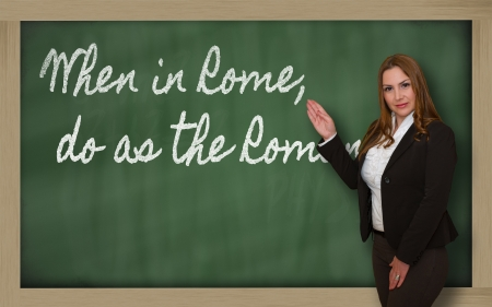 Successful, beautiful and confident woman showing When in Rome, do as the Romans do on blackboard Stock Photo - 18708128