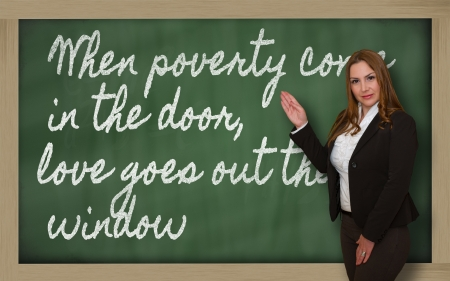 come in: Successful, beautiful and confident woman showing When poverty come in the door, love goes out the on blackboard Stock Photo