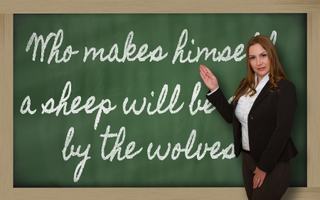 eaten: Successful, beautiful and confident woman showing Who makes himself a sheep will be eaten by the wolves on blackboard