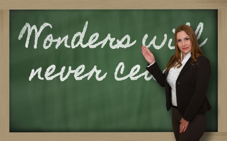 cease: Successful, beautiful and confident woman showing Wonders will never cease on blackboard