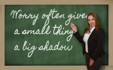 Successful, beautiful and confident woman showing Worry often gives a small thing a big shadow on blackboard photo