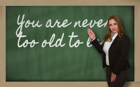Successful, beautiful and confident woman showing You are never too old to learn on blackboard photo