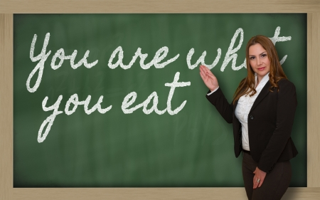 what to eat: Successful, beautiful and confident woman showing You are what you eat on blackboard Stock Photo